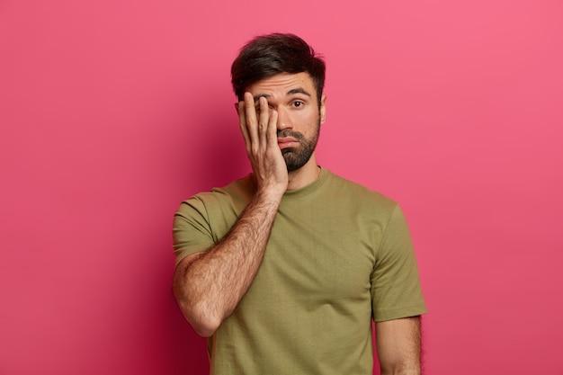 Усталый бородатый мужчина европеоидной расы закрывает лицо ладонью, смотрит с несчастным выражением лица, чувствует себя усталым и сонным, носит повседневную футболку, позирует на розовой стене, не хочет что-то делать