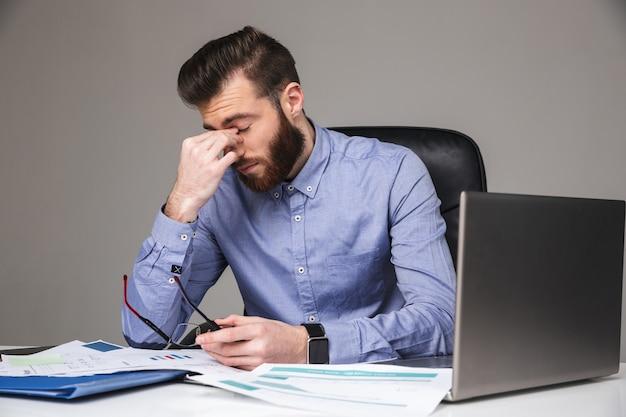 Усталый бородатый элегантный мужчина снимает очки, сидя за столом с закрытыми глазами в офисе