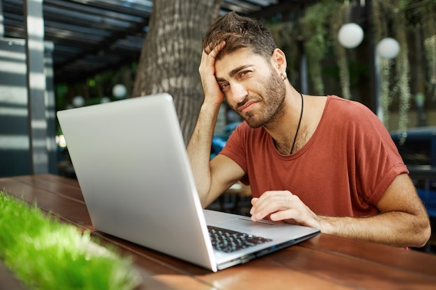 Tired bearded handsome freelancer, male programmer or student using laptop while sitting outdoor cafe
