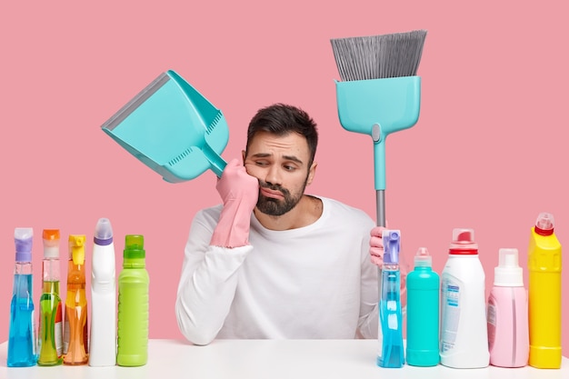 L'uomo barbuto stanco trasporta scopa, paletta, si sente stanco dopo aver spazzato e pulito il pavimento, si siede sul posto di lavoro con i detergenti