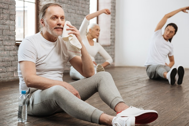 Tired bearded man sitting on the floor near bottle of water putting his arms on the legs while holding little towel in left hand
