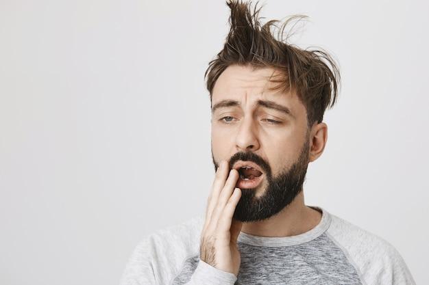 Uomo barbuto stanco con capelli disordinati che sbadiglia al mattino