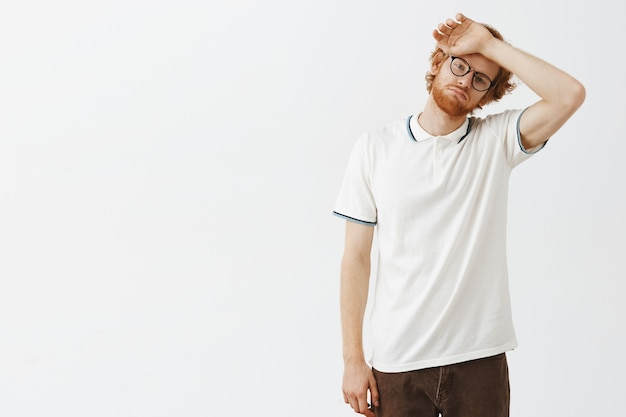 Ragazzo rosso barbuto stanco in posa contro il muro bianco con gli occhiali