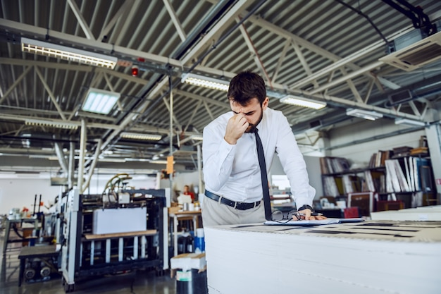 Tired bearded supervisor in shirt and tie standing in printing shop
