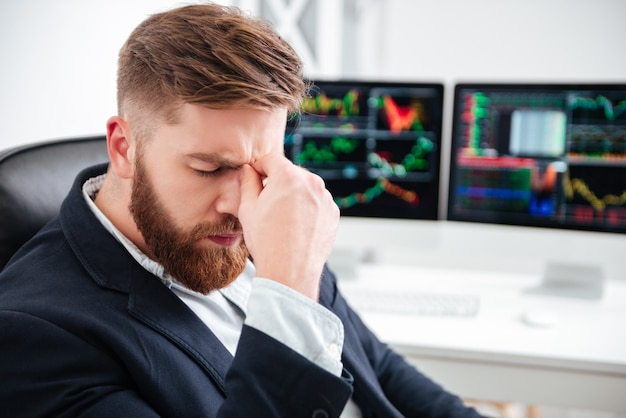 Усталый бородатый молодой бизнесмен сидит и болит голова в офисе