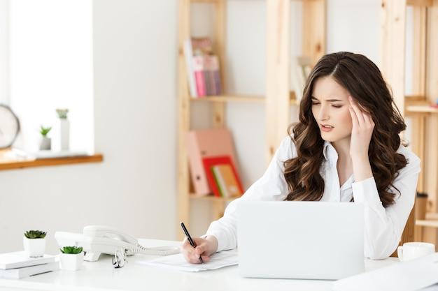 Усталая красивая бизнес-леди, держащая руку за голову, работая над компьютером и некоторыми деловыми документами в ярком офисе
