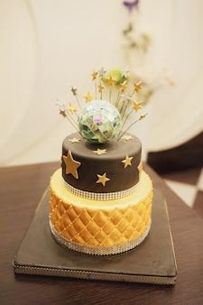 Tired birthday cake with golden glaze