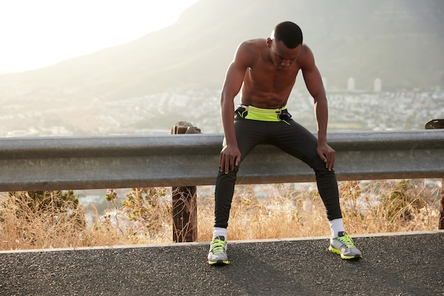 Tired black sportsman breathes with difficulty, rests with arms on knees, being fatigue after racing competition, wears leggings and comfortable shoes, copy space against mountain landscape.
