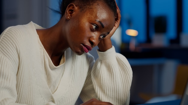 피곤한 흑인 여성은 늦은 밤 회사 사무실에서 노트북 작업을 하며 거의 낮잠을 자고 있습니다. 기한을 준수하여 프로젝트를 완료하기 위해 초과 근무를 하는 현대 기술을 사용하는 바쁜 직원