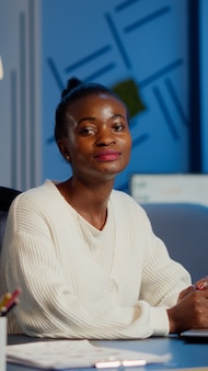Tired black woman manager looking at camera sighing after