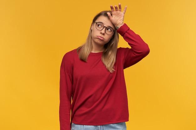 안경을 쓰고 피곤한 금발 소녀는 고립 된 이마 근처에 손등으로 서있는 왼쪽 상단을보고 뺨을 부풀려