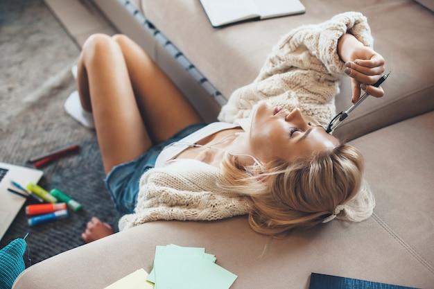 Усталая блондинка сидит на полу и занимается домашним обучением с помощью ноутбука