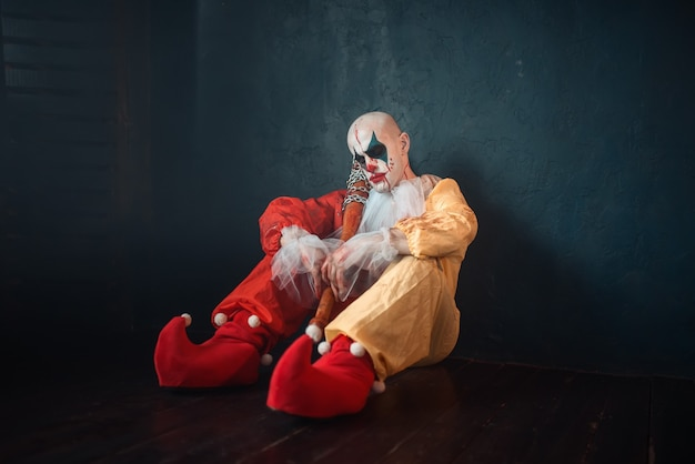 Tired bloody clown with baseball bat sitting on the floor.
