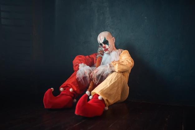 Усталый кровавый клоун с бейсбольной битой сидит на полу.