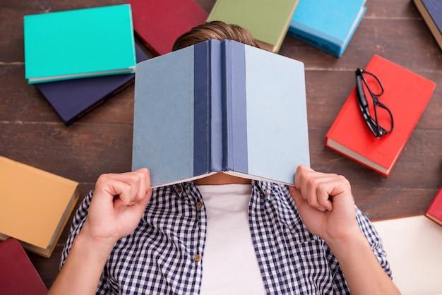 피곤한 책벌레. 그의 주위에 많은 다채로운 책이 놓여 있는 단단한 나무 바닥에 누워 있는 동안 책으로 얼굴을 덮고 있는 젊은 남자의 상위 뷰