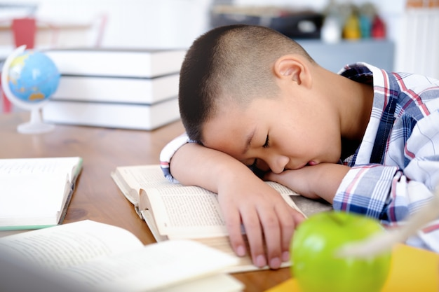 Tired and bored boy sleeping among the books.
