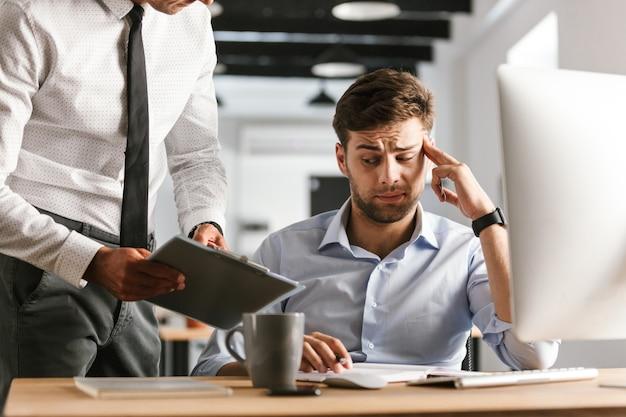 문서와 클립 보드를 보여주는 그의 동료 근처 컴퓨터 작업 사무실에 앉아 피곤 지루 불쾌한 남자.