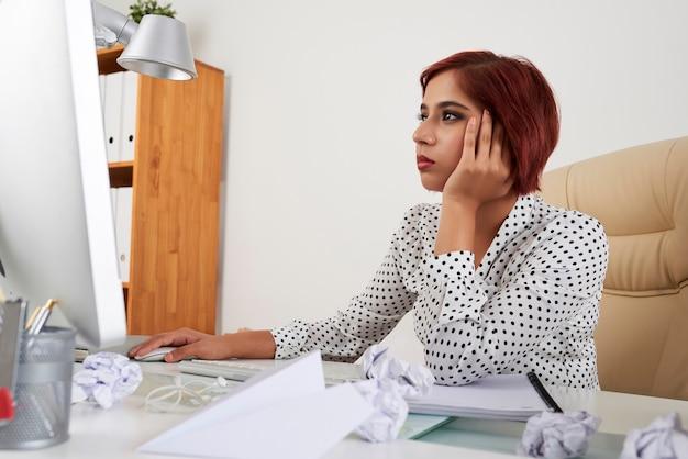 コンピューターの画面で記事を読んだり、レポートに取り組んでいる疲れた退屈な女性サラリーマン