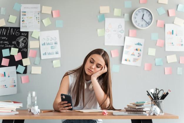 스티커와 함께 회색 벽의 배경에 테이블에 앉아 전화로 피곤하고 지루한 소녀. 학습 개념.