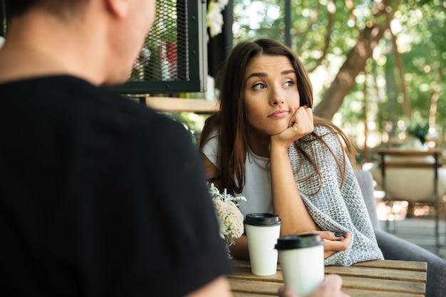 Уставшая скучающая женщина сидит и пьет кофе