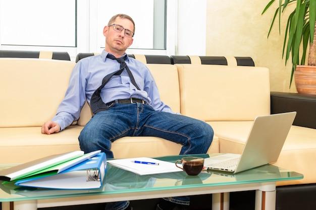 Усталый бизнесмен босс после тяжелой работы откинулся на спинку дивана. тяжелая работа. подготовка отчета.