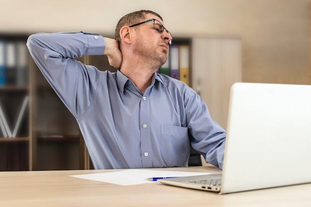 Усталый босс, бизнесмен, цепляясь за шею за столом, испытывает крабовую боль в шее