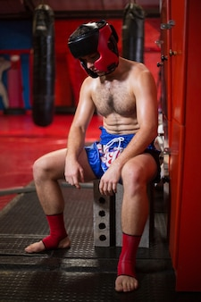 Tired boxer sitting in locker room