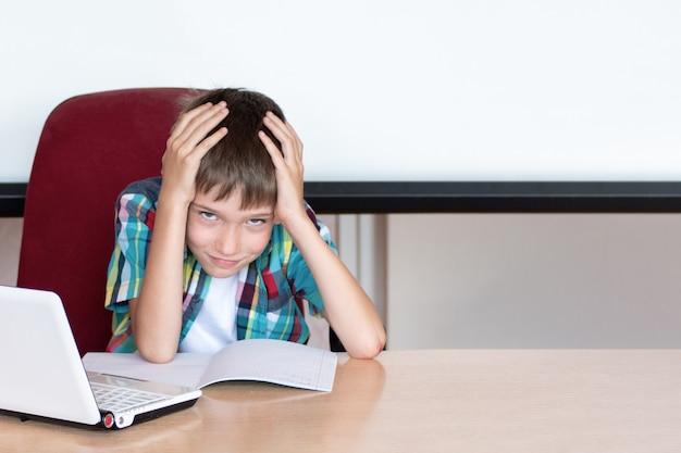 숙제를 하기 위해 머리를 잡고 있는 피곤한 소년. 학습 장애를 가진 아이. 숙제에 문제가 있는 소년. 교육 개념, 다시 학교로. 복사 공간