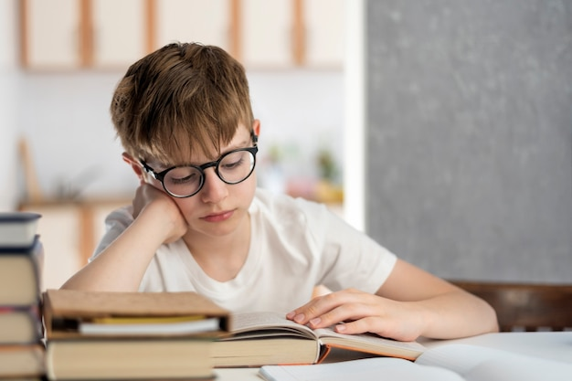 眼鏡をかけた疲れた少年は本を読みます。子供はたくさんの宿題をしている。ホームスクーリング。通信教育。