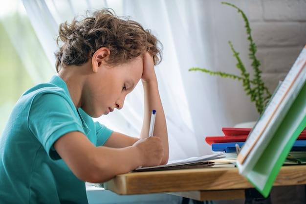 疲れた少年が頭に手を置いて目をそらし、机に座ってレッスンをしている