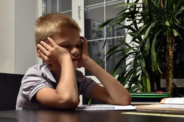 Утомленный мальчик сидит дома вечером. ненавистная домашняя работа.
