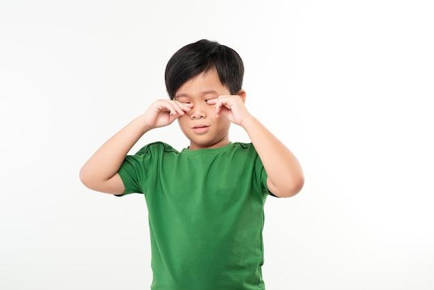 Усталый мальчик. ребенок трет глаза.