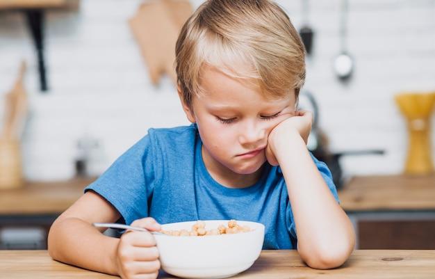 Усталый мальчик пытается съесть его хлопья