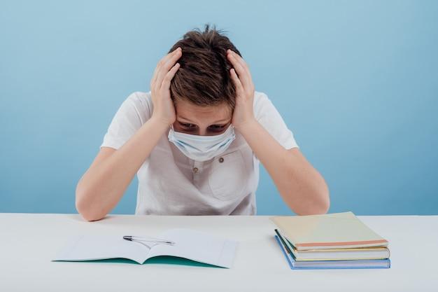 파란색 배경에 격리된 탁자에 앉아 머리에 손을 대고 의료 마스크를 쓴 피곤한 소년