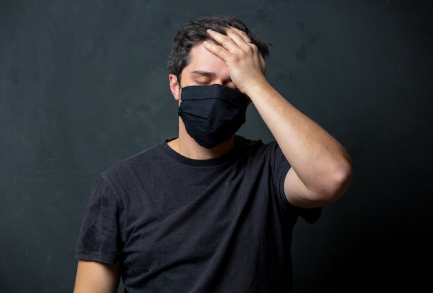 Tired brunet man in in black facemask on dark wall