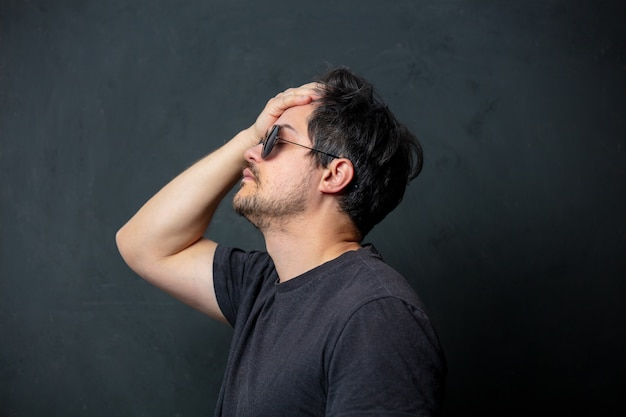 Tired brunet man in black t-shirt and sunglasses on dark wall