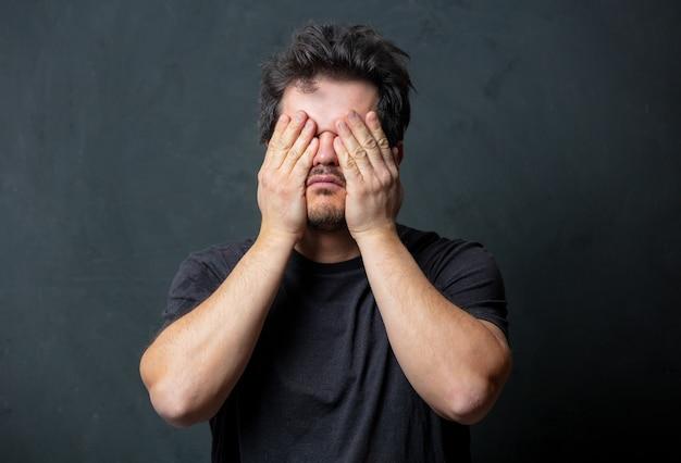 暗い壁に黒いtシャツを着た疲れた黒髪の男