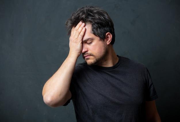 Усталый брюнет в черной футболке на темной стене