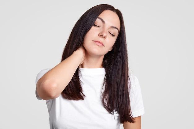 피곤한 갈색 머리 여성은 앉아있는 생활 방식을 가지고 목에 통증을 느끼고 신체 활동이 필요하며 눈을 감고 잠을 원합니다.
