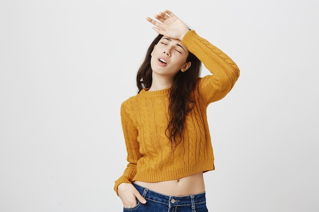 セーターのため息で疲れたブルネットの少女、目を閉じ、疲れきった額に手をかざす