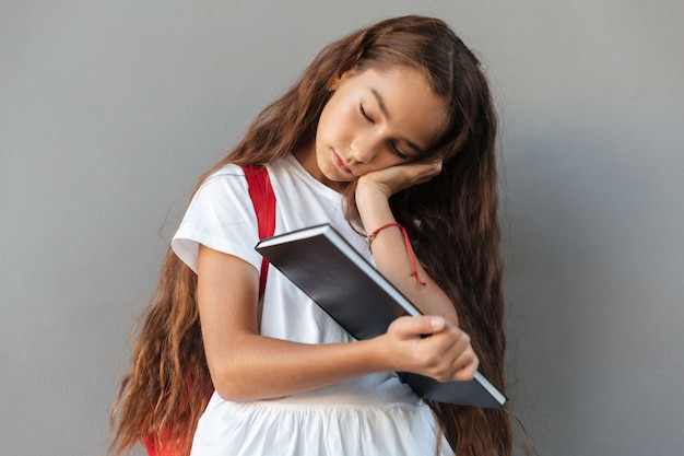 Tired brunette schoolgirl with long hair sleeping on book