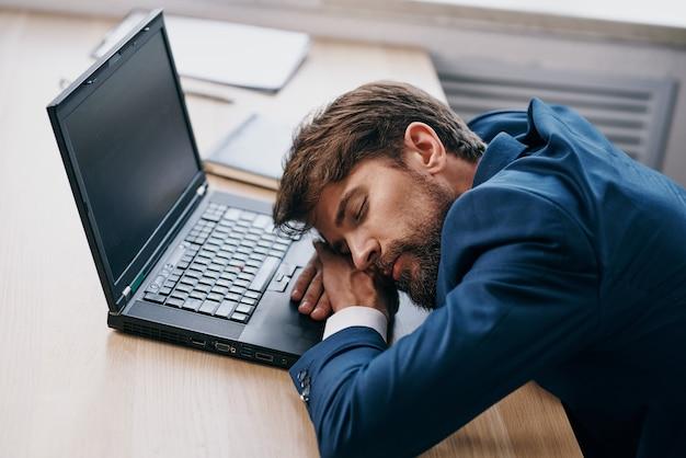 Усталый деловой человек перед ноутбуком в офисе