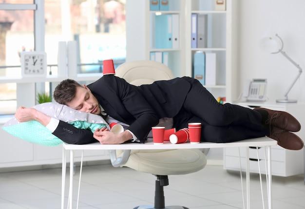 Усталый деловой человек спит среди пустых бумажных кофейных чашек на рабочем столе в офисе