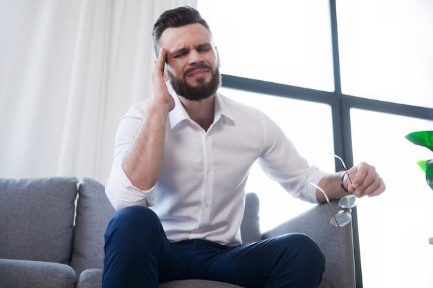 Усталый деловой человек со стрессом страдает головной болью и сидит на диване с болью на лице