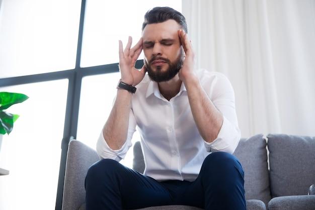 ストレスで疲れたビジネスマンは頭痛があり、顔に痛みを伴うソファに座っています