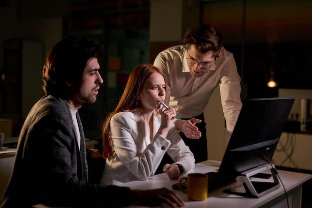 피곤한 비즈니스 사람들은 밤에 데스크탑 컴퓨터를 사용하여 특정 작업, 계정 처리 및 전략적 이동에 대해 설명합니다. 큰 기업 사무실에서 밤 늦게 사람들