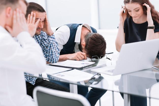 Усталая бизнес-команда обсуждает проблемы нового стартапа. рабочие будни