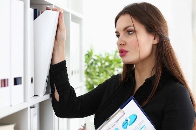 Tired business woman clerk holding folders