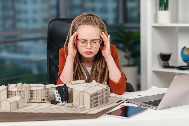 Усталая деловая женщина чувствует головную боль по поводу крайнего срока сдачи архитектурного и дизайнерского проекта