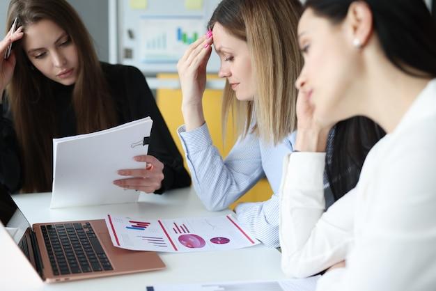 疲れたビジネス女性はテーブルで思慮深い状態で座っています